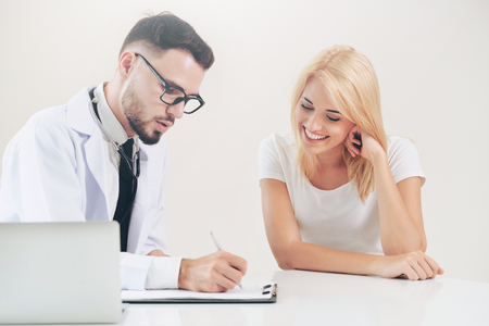 Male doctor talks to female patient in hospital office while writing on the patients health record on the table. Healthcare and medical service. 版權商用圖片