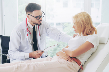 Male doctor is talking and examining female patient in hospital office. Healthcare and medical service. Stock Photo