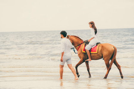 Young couple goes honeymoon horse riding on the beach in summer vacation. Standard-Bild