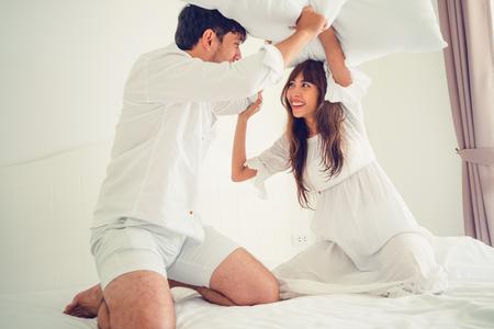 Happy couple do pillow fighting in home bedroom. Reklamní fotografie