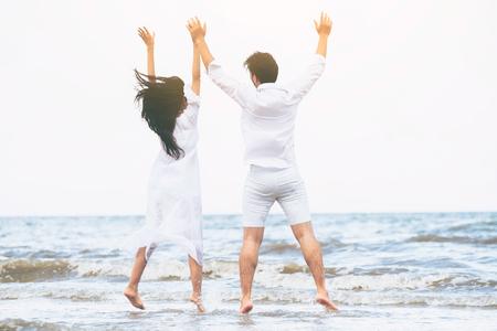 Feliz pareja va viajes de luna de miel en la playa de arena tropical en verano. Foto de archivo