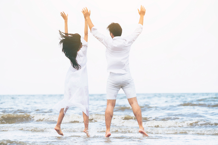 Happy couple going honeymoon travel on tropical sand beach in summer. Stock Photo