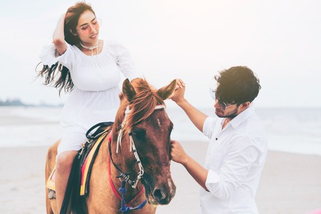 Young couple goes honeymoon horse riding on the beach in summer vacation. Imagens