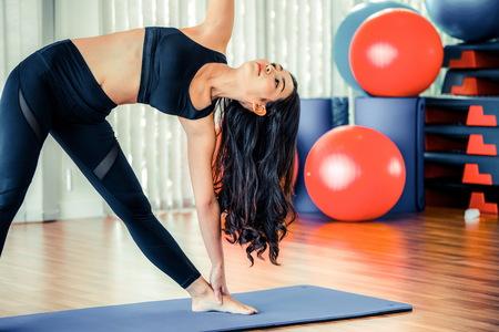 Mujer joven practicando posición de yoga en un estudio de gimnasio interior. Concepto de estilo de vida saludable y bienestar.