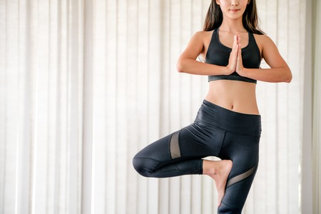Young woman practicing yoga position in an indoor gym studio. Healthy and wellness lifestyle concept. Stock Photo
