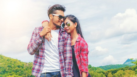 Happy couple take a romantic walk in green grass field on the hills. Travel and honeymoon concept.