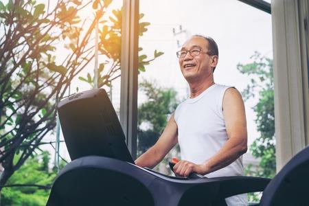 Starszy mężczyzna ćwiczenia na bieżni w centrum fitness. Dojrzały zdrowy styl życia. Zdjęcie Seryjne