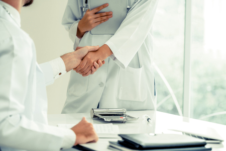 Doctor at the hospital giving handshake to another doctor showing success and teamwork of professional healthcare staff. 版權商用圖片