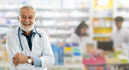 Senior male pharmacist working at the pharmacy. Medical healthcare and pharmaceutical service. Фото со стока