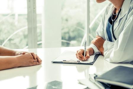 La doctora habla con la paciente mientras escribe en el registro de salud del paciente en la oficina del hospital. Servicio sanitario y médico. Foto de archivo