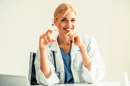 Happy woman doctor holding syringe and sitting in hospital office. Healthcare and medical service.