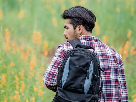 Young man travel in nature and hills landscape with backpack.