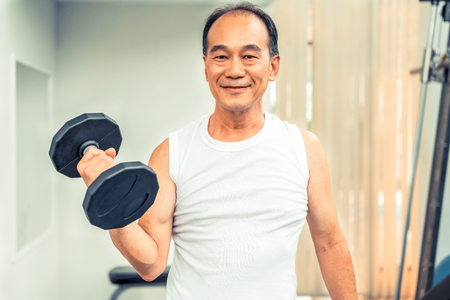 Senior man lifting dumbbell in fitness gym. Senior healthy lifestyle.