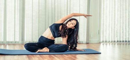Young woman practicing yoga position in an indoor gym studio. Healthy and wellness lifestyle concept. 免版税图像