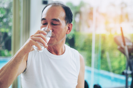 Senior man drink mineral water in gym fitness center after exercise. Elderly healthy lifestyle. Фото со стока - 112077385