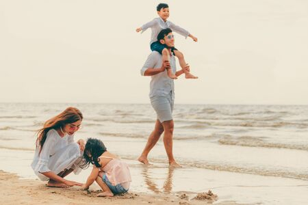 Happy family of father, mother and kids goes vacation on a tropical sand beach in summer. Reklamní fotografie