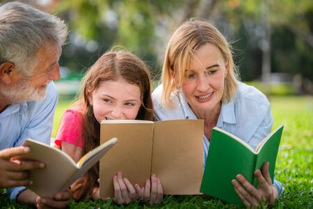 Happy family read books together and lying on green grass in public park. Little girl kid learning with mother and father in outdoors garden. Education and family lifestyle.