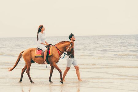 Young couple goes honeymoon horse riding on the beach in summer vacation.