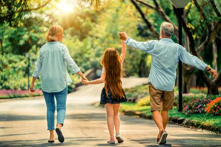 Happy healthy family walk together on path in the park in summer. Concept of family bonding. Imagens