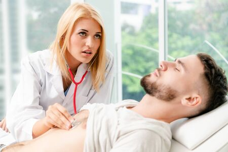 Woman doctor is talking and examining male patient in hospital office. Healthcare and medical service. Banque d'images - 133679919