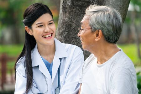 Friendly doctor taking care of senior man in the hospital garden. Medical and healthcare doctor service concept. 版權商用圖片