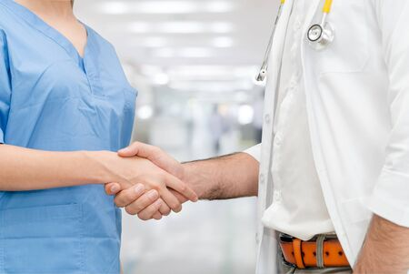 Doctor in hospital handshake with another doctor. Healthcare people teamwork and medical service concept. Standard-Bild