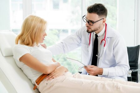 Male doctor is talking and examining female patient in hospital office. Healthcare and medical service. Banque d'images - 133680382