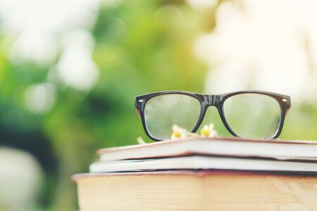 Soft focus retro style books and eye glasses with nature background. Reading and education concept.