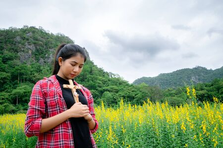 Young beautiful woman praying on nature background. Hope and faith concept. 版權商用圖片