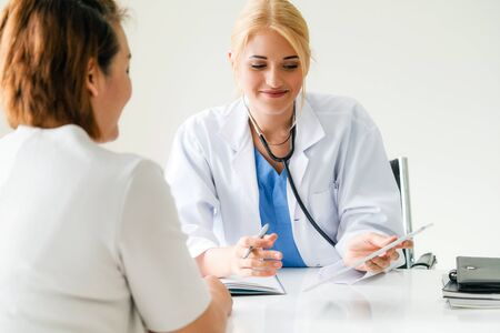 Woman doctor is talking and examining female patient in hospital office. Healthcare and medical service. Stock Photo