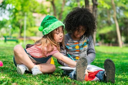 School boy and girl reading book together in the park. Education and friends concept. Standard-Bild