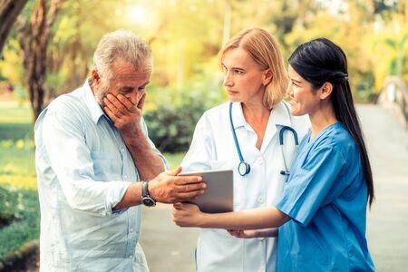Senior man in gesprek met arts, verpleegkundige of verzorger in het park. Volwassen mensen gezondheidszorg en medisch personeel dienstverleningsconcept.