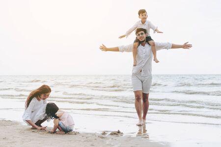 아버지, 어머니와 아이들의 행복한 가족은 여름에 열대 모래 해변에서 휴가를 간다.