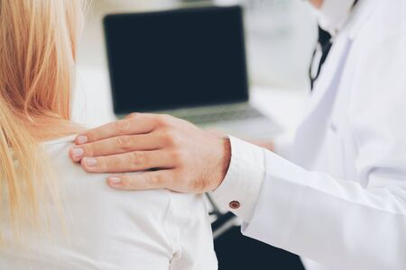 Male doctor talks to female patient in hospital office while looking at the patients health data on laptop computer on the table. Healthcare and medical service. Stock Photo