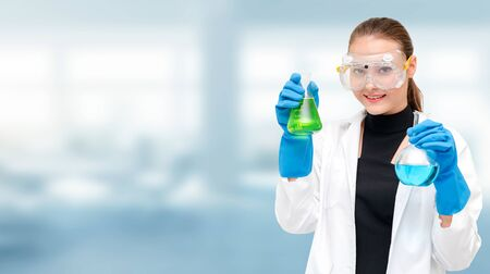 Retrato de joven científico o químico feliz con tubo de ensayo en laboratorio. Concepto de investigación y desarrollo de tecnología química o médica. Foto de archivo