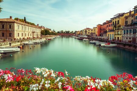Colorful town of Peschiera del Garda with boats and blurred geranium flowers. The city is located at lake Lago di Garda,East of Venice, Italy, Europe.