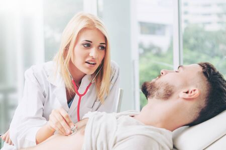 Woman doctor is talking and examining male patient in hospital office. Healthcare and medical service. Banque d'images - 133527108