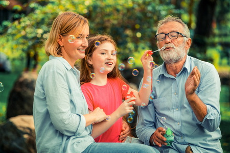 Happy family blows soap bubbles together while going vacation on weekend in the garden park in summer. 스톡 콘텐츠