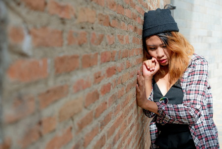 Depressed teenage woman feeling sad alone against brick wall in old town.