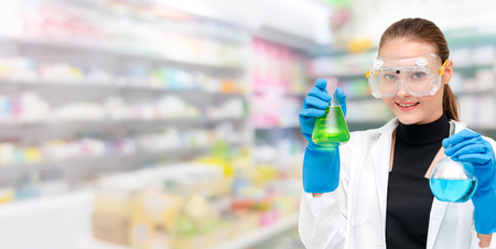 Portrait of young happy scientist or chemist holding test tube in laboratory. Chemical or medical technology research and development concept. Stock Photo