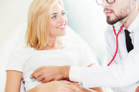 Male doctor is talking and examining female patient in hospital office. Healthcare and medical service. 스톡 콘텐츠