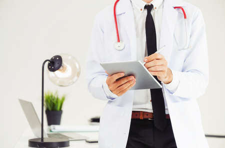 Doctor working on tablet computer at office in the hospital. Medical and healthcare concept. Stock Photo
