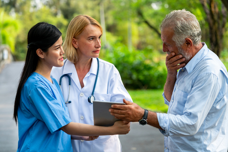 Senior man talking to doctor, nurse or caregiver in the park. Mature people healthcare and medical staff service concept.