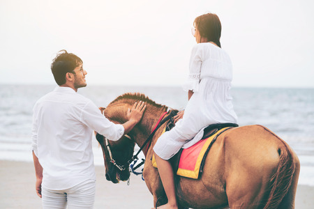 Young couple goes honeymoon horse riding on the beach in summer vacation. Banco de Imagens - 116324366