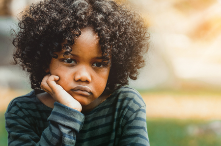 Unhappy bored little african american kid sitting in the park. The boy showing negative emotion. Child trouble concept. Фото со стока - 116325078