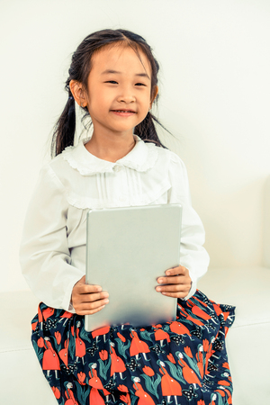 Little happy kid on white background with tablet computer. Childhood lifestyle.