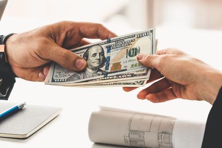 Zakenmanhand die geld verzendt naar een andere bedrijfspersoon. Transactie, betaling, salaris en bankconcept. Stockfoto