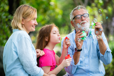 Happy family blows soap bubbles together while going vacation on weekend in the garden park in summer. Kid education and family activities concept.