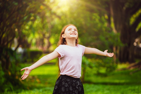 Happy cute little girl playing in the outdoor park in summer. Child expression and lifestyle.