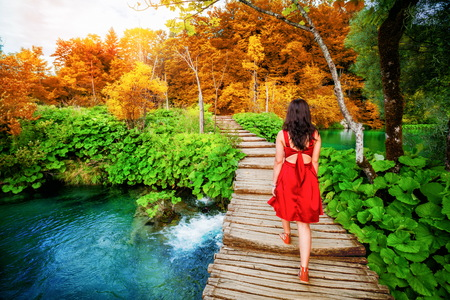 Woman traveler walking on wooden path trail with lakes and waterfall landscape in Plitvice Lakes National Park, and famous travel destination of Croatia. Foto de archivo - 116528137